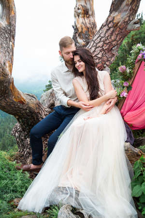 fine art: Couple in love, gorgeous bride and stylish groom on top, fine art wedding couple, luxury ceremony at mountains with amazing view and decorations with flowers.