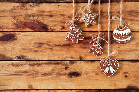 Gingerbread cookies hanging over dark old wooden background. Flat lay, top view, with copy space. X-mas background.