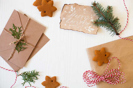 Christmas composition. Xmas cookies, Gingerbread man, ribbon, card, festive decoration, fir branches on white wooden background. Flat lay, top view, with copy space. Close Up Stock Photo