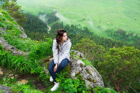 unrecognisable people: Beautiful woman sitting on mountain top and contemplating landscape Stock Photo