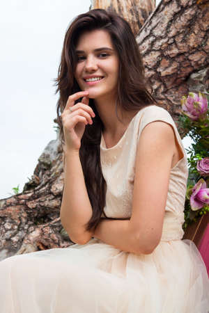 Beautiful young bride sitting near rocks against background the mountains, wedding inspiration