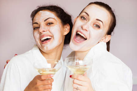 Smiling girlfriends with champagne in the spa salon Stockfoto