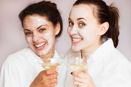 Smiling girlfriends with champagne in the spa salon Stok Fotoğraf