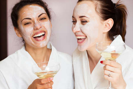 Smiling girlfriends with champagne in the spa salon Standard-Bild