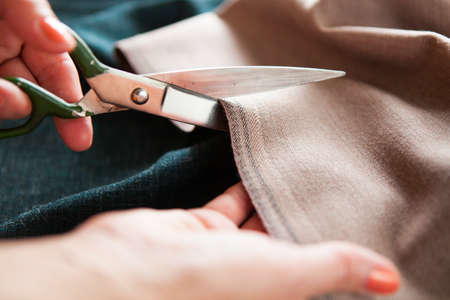 notch: Tailor. Woman Hands notch tailor tailors scissors cloth. Close Up.   Stock Photo