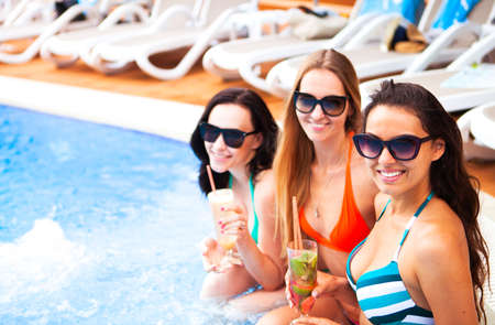 Happy girls with beverages on summer party near the pool, summer time! Stockfoto