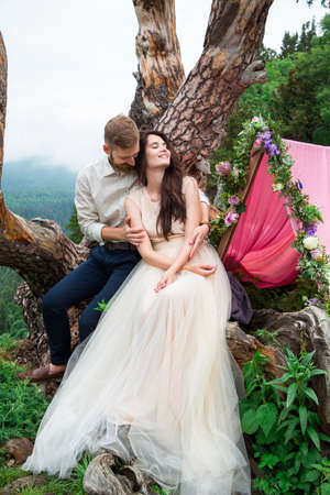 Couple in love, gorgeous bride and stylish groom on top, fine art wedding couple, luxury ceremony at mountains with amazing view and decorations arcs with flowers.