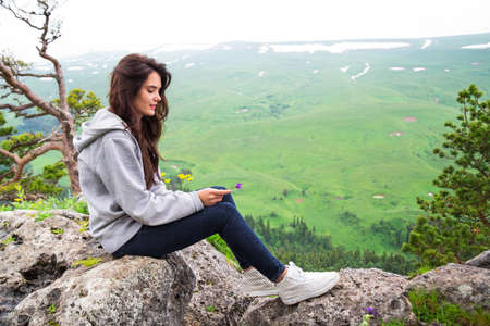 Beautiful woman sitting on mountain top and contemplating landscape Stock Photo