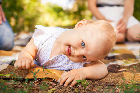 Outdoor portrait of a baby on all fours. crawling on knees child on the grass in a summer park, set