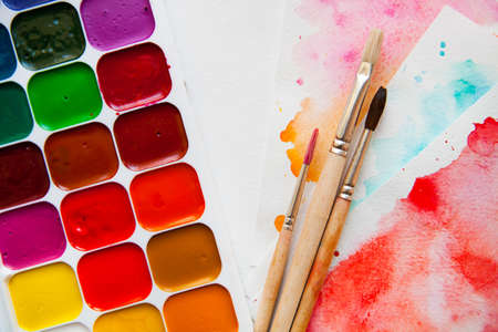 pallette: Palette of watercolor paints, brushes and paper for a water color on white background, close up.