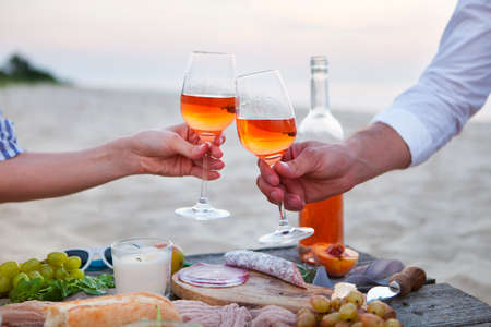 Man and woman clanging wine glasses with rose wine at picnic sunset beach, romantic concept Archivio Fotografico