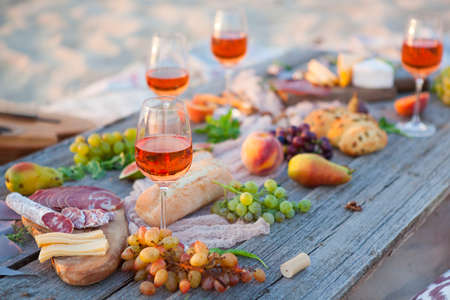 Picnic on the beach at sunset in the style of boho, food and drink conception Archivio Fotografico