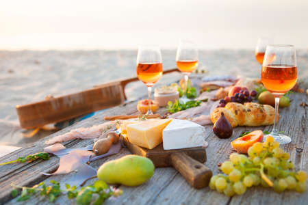 Picnic on the beach at sunset in the style of boho, food and drink conception Stock Photo