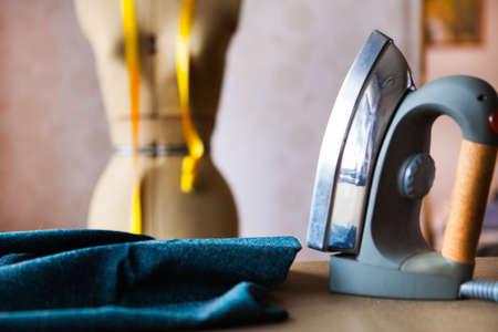 Sluit omhoog van professioneel ijzer in de fabriek van een kleermaker, die thema aanpassen