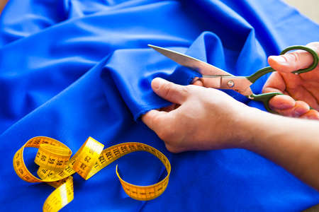 Tailor. Man Hands notch tailor tailors scissors cloth. Close Up. Stok Fotoğraf