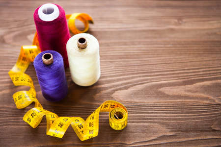 Tailoring. Tape measure and colorful thread on dark wooden background, flat lay. Set Stock Photo