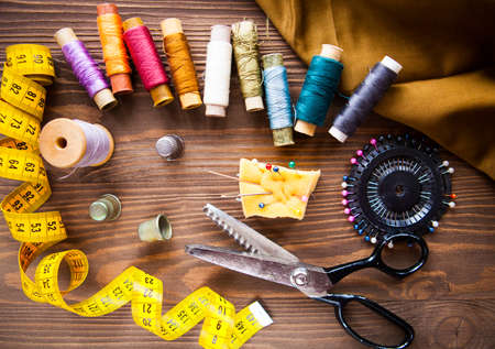 tailored: Scissor, buttons, zip, tape measure, thread and thimble on fabrics on dark wooden background, flat lay. Set Stock Photo