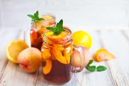 Homemade iced lemonade with ripe peaches and fresh mint. Fresh peach ice tea in a mason jar. Copy space background. Stock Photo
