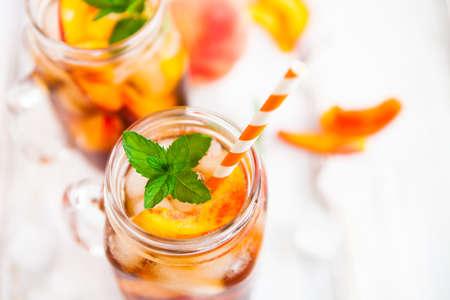 Homemade iced lemonade with ripe  peaches and fresh mint. Fresh peach ice tea in a mason jar. Copy space background.