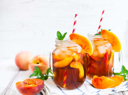 Homemade iced lemonade with ripe  peaches and fresh mint. Fresh peach ice tea in a mason jar. Copy space background.