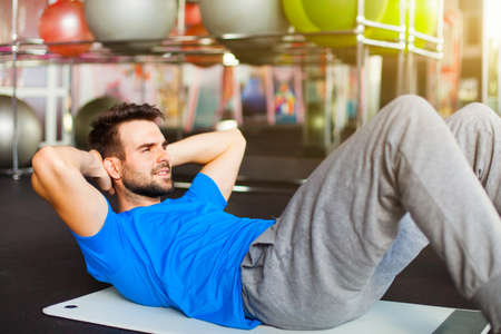 Young fit man exercising in a crossfit gym, Muscular man doing abdominal crunches Stock Photo