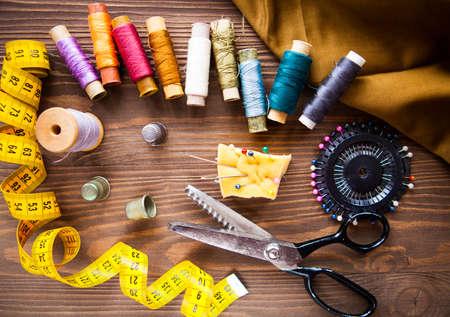Scissor, Knöpfe, Reißverschluss, Maßband, Thread und Fingerhut auf Geweben auf dunklem hölzernem Hintergrund, flache Lage. einstellen