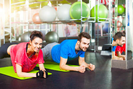 Sport - young fitness couple in crossfit gym. Sport couple doing pushups bar on floor in the gym.