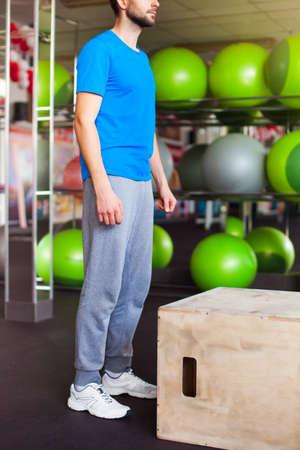 hombre atlético con la cara intensa y la barba que llevaba una camiseta azul realizar dramático cuadro de crossfit salto