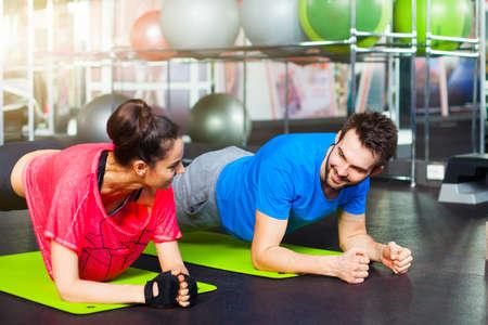 スポーツ - crossfit ジムでフィットネスの若いカップル。ジムの床で腕立て伏せバーを行うスポーツ カップル。 写真素材