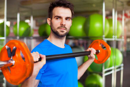 Muscular man lifting barbell in crossfit club Stock Photo