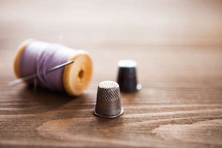 Vintage spool of thread with needle closeup. Tailors work table, textile or fine cloth making. Horizontal Stock Photo