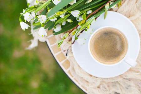Bouquet White spring bellflowers and coffee cup on table in garden. Spring morning with coffee. Stock Photo
