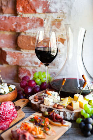 Wine snack set. Glass of red wine, grape, cheese, over rustic wooden background. Top view, copy space, horizontal composition. Stock Photo