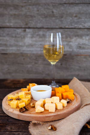 comb: Grape, cheese, figs and honey with a glass of white wine on wood background Stock Photo