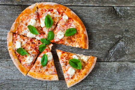 Homemade Pizza with tomato sauce, artichoke hearts, olives, Parmacotto, fresh mozzarella, parmesan and basil on the grey wooden rusty background Standard-Bild