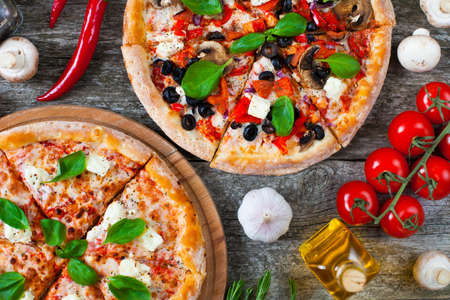Homemade Pizza with tomato sauce, artichoke hearts, olives, Parmacotto, fresh mozzarella, parmesan and basil on the grey wooden rusty background Stockfoto