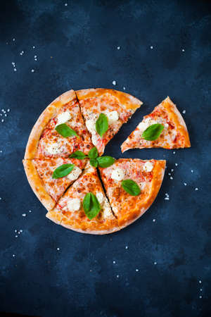 Pizza Four cheeses with tomato sauce, olives,  fresh mozzarella, parmesan and basil on the dark concrete background