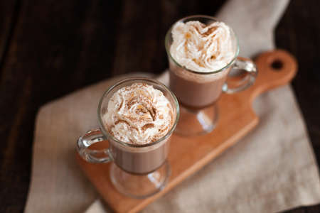Two glasses with Hot chocolate garnished with whipped cream and cocoa powder. Stock Photo