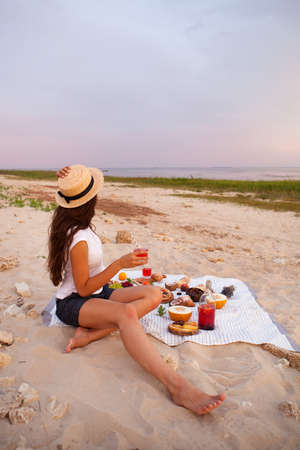 Young woman in Summer Picnic on the beach at sunset in the white plaid, food and drink conception.