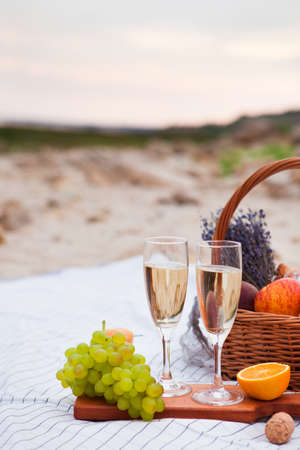 Two glasses of champagne. Summer Picnic on the beach at sunset in the white plaid, food and drink conception.