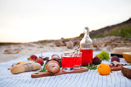 Homamade berry lemonade. Summer Picnic on the beach at sunset in the white plaid, food and drink conception. Standard-Bild