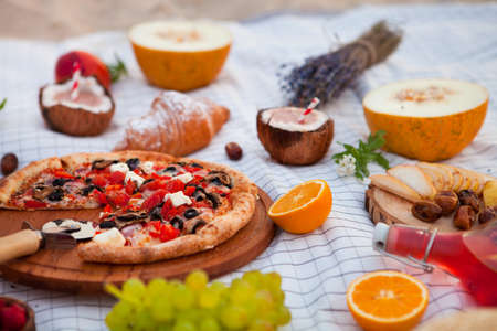 Summer Picnic: pizza and various fruits on the beach at sunset in the white plaid, food and drink conception. Stock Photo