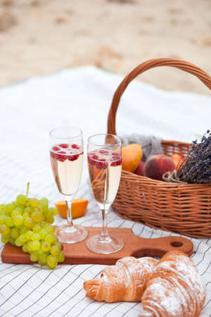 Two glasses of champagne with raspberry. Summer Picnic on the beach at sunset in the white plaid, food and drink conception.
