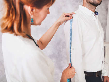 Woman tailor takes measures with male models. Mid section portrait of tailor fitting bespoke suit to model Stock Photo