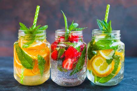 Verse limonade met zomerfruit en bessen op donkere betonnen achtergrond Stockfoto