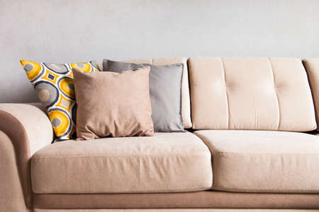 Multi-colored pillows on a beige fabric sofa, the concept of home comfort and cozy, copy space, close-up 版權商用圖片