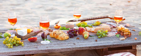 Picnic on the beach at sunset in boho style. Romantic dinner, friends party, summertime, food and drink conception Stock fotó