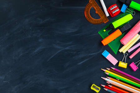 Back To School concept. School supplies on blackboard background, accessories for the schoolroom - pencils, scissors, chalk, markers. Ð¡opy space top view