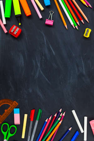 Back To School concept. School supplies on blackboard background, accessories for the schoolroom - pencils, scissors, chalk, markers. Сopy space top view Stock Photo