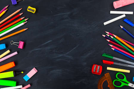 Back To School concept. School supplies on blackboard background, accessories for the schoolroom - pencils, scissors, chalk, markers. ?opy space top view